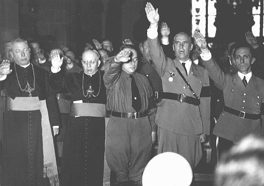 Hajlující nacističtí pohlaváři (vpravo Joseph Goebbels, druhý zprava Wilhelm Frick) a katoličtí duchovní. Německo, datum neznámé. (Bayerische Staatsbibliotek)