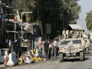 A convoy of U.S. armoured vehicles move past the scene of bomb attacks in Baghdad
