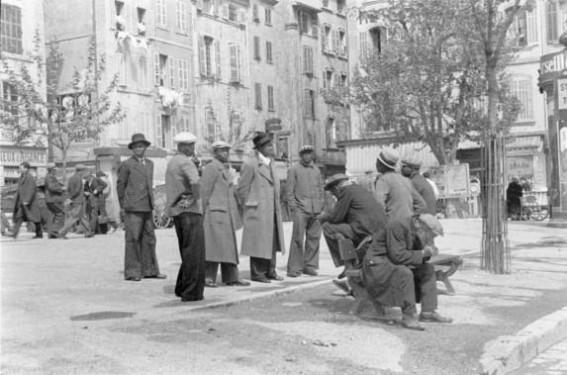 5FK-M1-Z2-1938-2  Marseille, Strassenszene / Foto  Marseille (Dep. Bouches-du-Rhone, Frankreich). - Strassenszene: Gruppe von Afrikanern auf einem Platz der Stadt. - Foto, 1938(?).  F:  Marseille / Scene de rue / Photo  Marseille (Bouches-du-Rhone) - Scene de rue : groupe d'Africains sur une place de la ville. - Photo, 1938 (?).