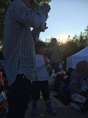 Ásotthalom camp v podvečer. Stále se na silnici, směřující od srbské hranice, vynořují a přichází další skupinky uprchlíků