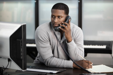 Black man using computer and talking on telephone
